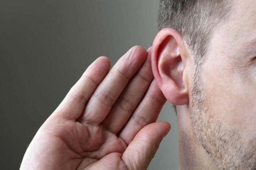 Man placing his hand to his ear