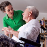 Aide helping resident