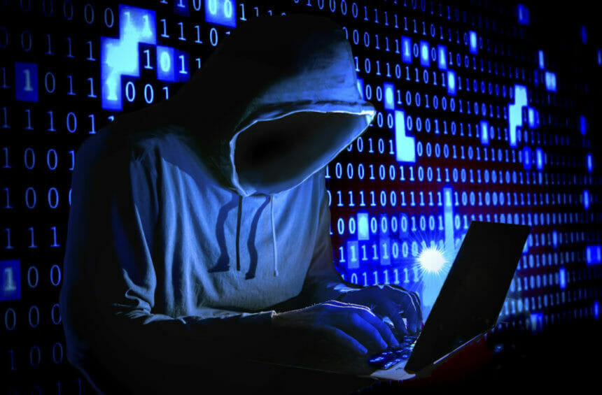 hooded hacker at a laptop