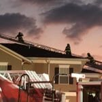 Three firefighters on the roof of Heather Glen Senior Living.
