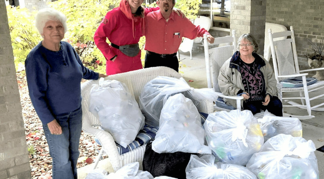 People standing by bags of donations.