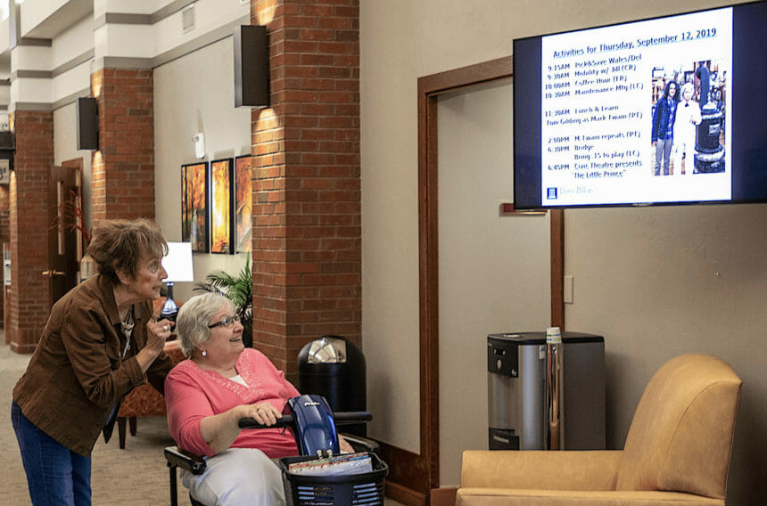 senior living resident and guest look at tv screen