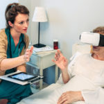 Healthcare worker using virtual reality with senior