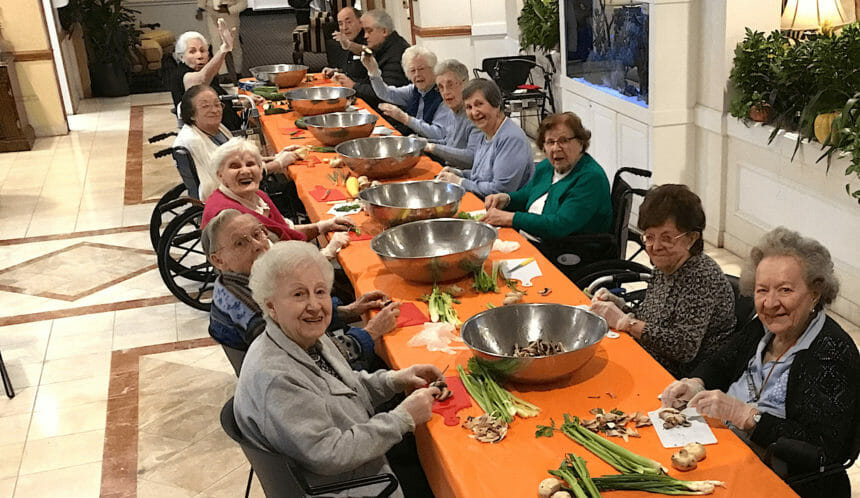 Residents at a table cutting vegetables.