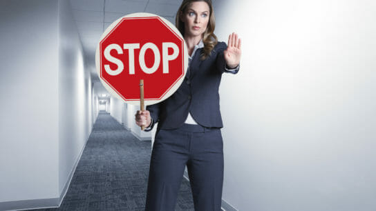 Woman holding stop sign in a hallway