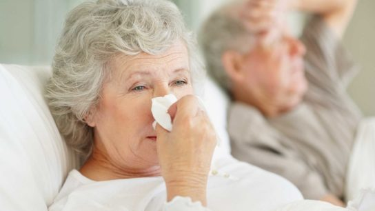 older woman wiping her nose with a tissue