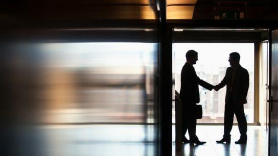 Businessmen shaking hands in corridor