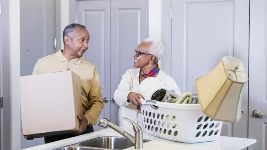 A senior African-American couple moving into a new home. They walked through the doorway carrying a box and laundry basket full of personal items and set them on the kitchen counter. They are looking at each other.