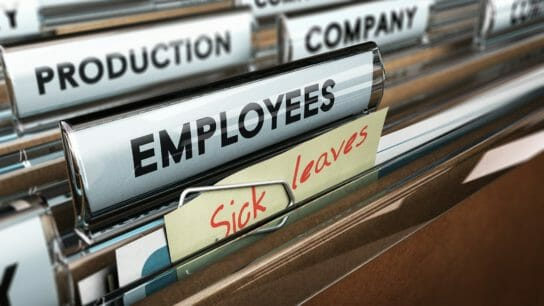 Close up on a file tab with the word employees plus a note with the text sick leaves, blur effect at the background. Concept image for illustration of sick leave