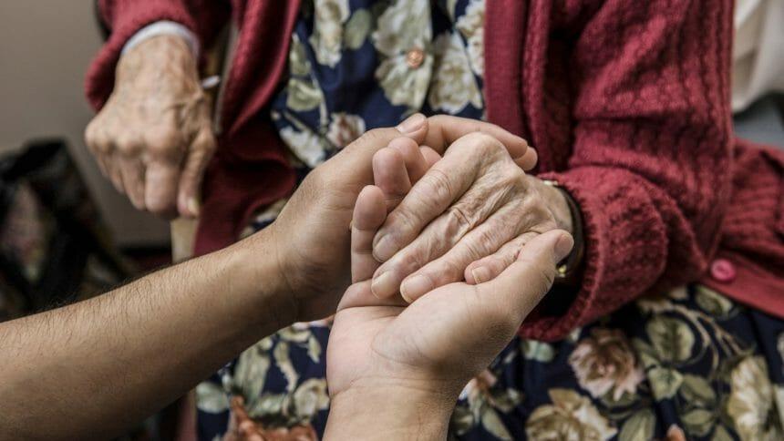 Nurse holding hands with elderly patient.