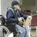 Eldery male beggar sat in wheelchair begging for money.