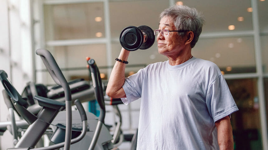 Asian man lifting weight in exercise room