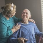 Family caregiver with disabled elderly man