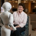 Pepper the robot talking to a woman in a chair.