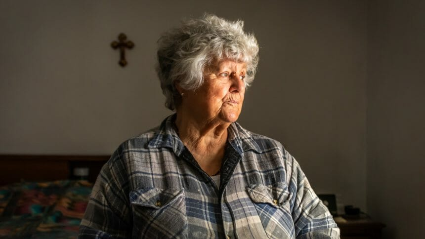 Portrait of an elderly Portuguese woman sitting on a bed by a window in her room.