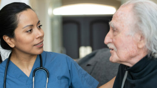 healthcare worker talking with older man