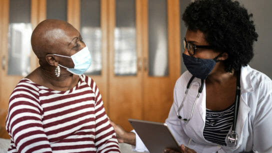 Black healthcare worker talking with Black woman