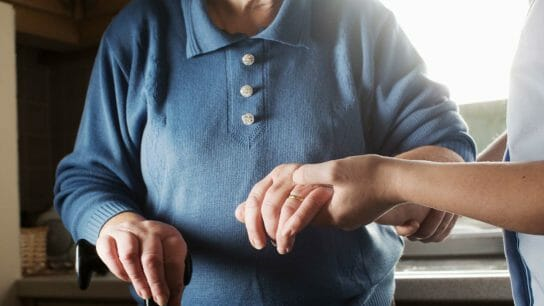 a worker holding an older adult's hand