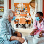 Healthcare worker at home with older man