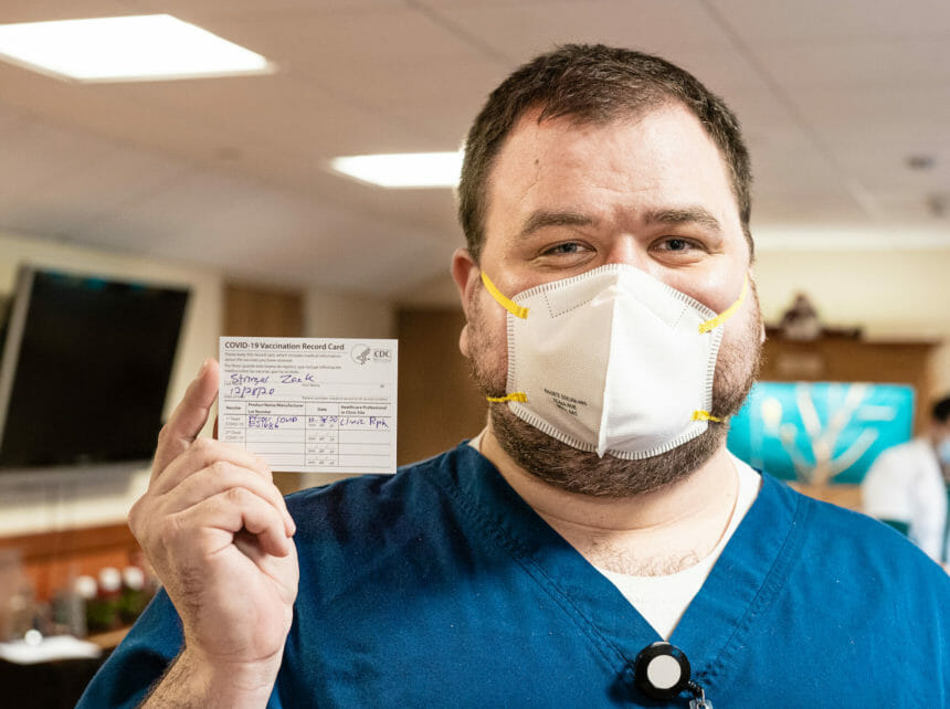 man wearing mask holding up his vaccination card