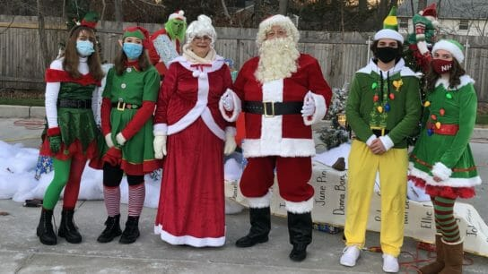 Mr. & Mrs. Claus surrounded by elves