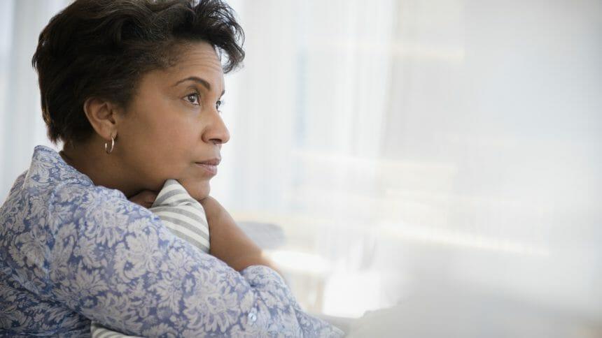 Pensive older Black woman clutching pillow