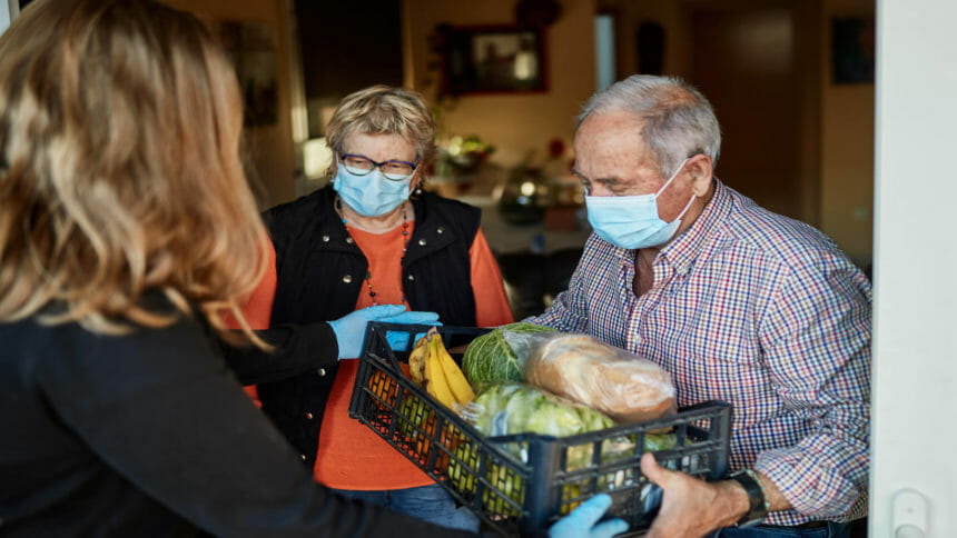 Older couple at home receives container filled with fresh food
