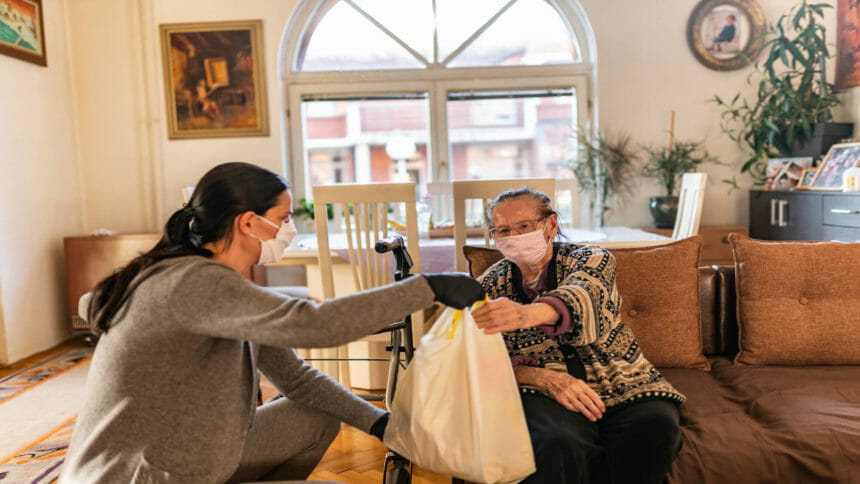 Worker delivers bag of groceries to older woman at home