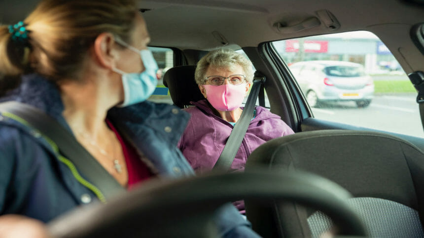 masked woman driving an older woman who has a mask on