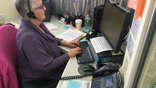 woman at Aroostook Agency on Aging works at her desk