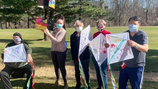 older adults and caregivers flying kites