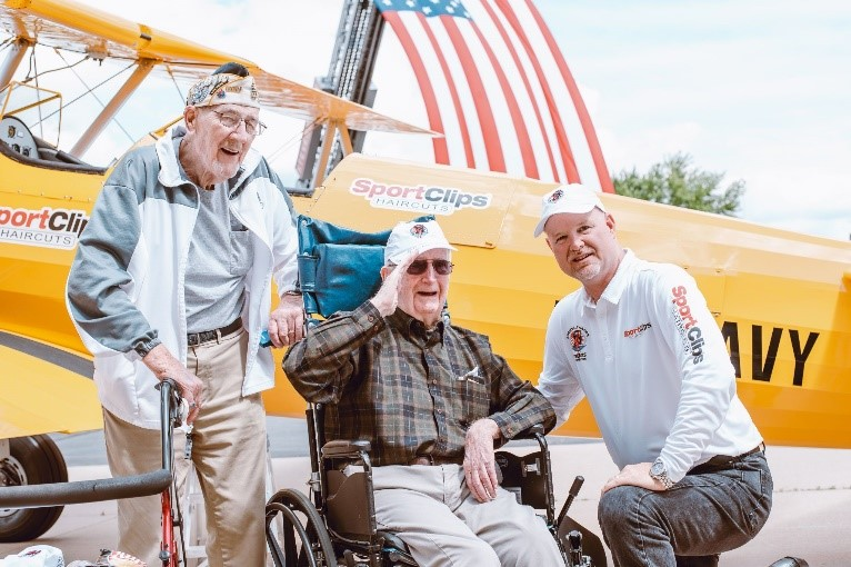 Veterans saluting in front of a Dream Flights plane.