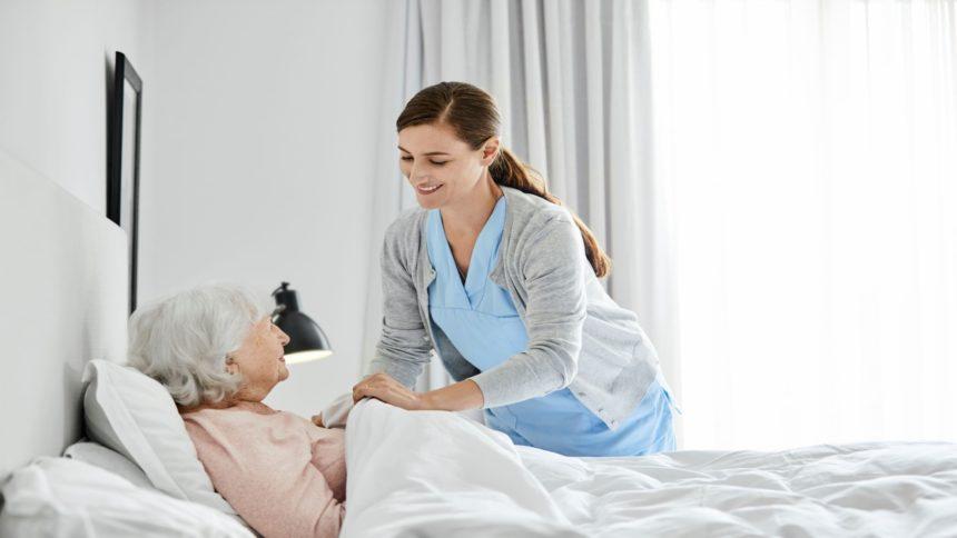 Caretaker tending to woman in her bed