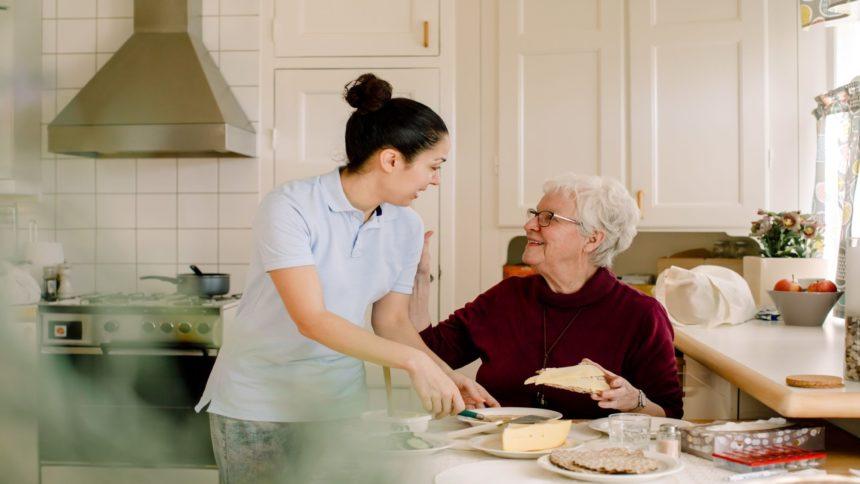 Elderly woman in kitchen with her caretaker