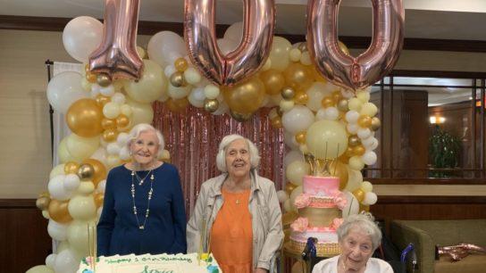 Atria's Golden Girls smiling by a birthday cake