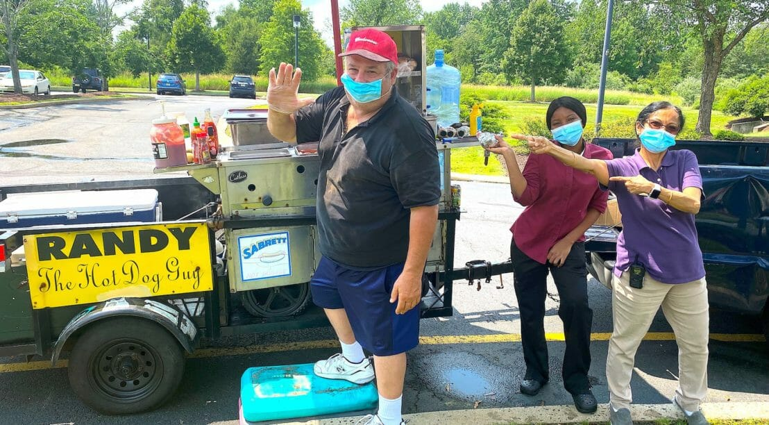 man standing at hot dog cart with two women