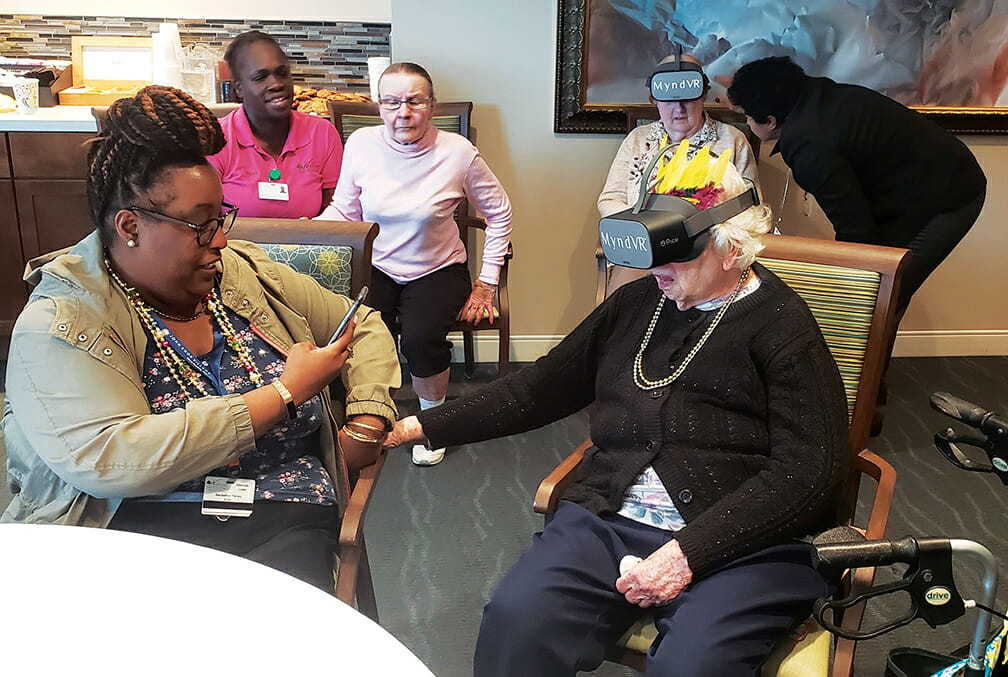 Image of residents sharing virtual reality experiences with care providers.