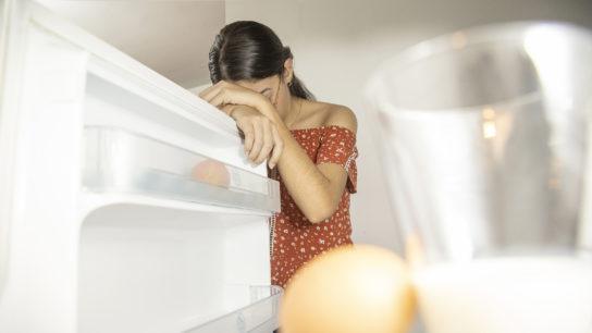 woman looking into almost empty refrigerator