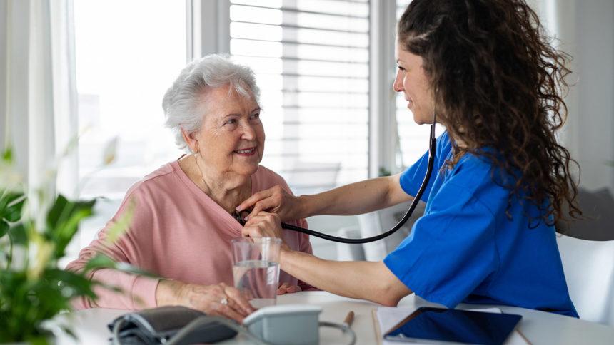Nurse in blue scrubs checks older woman using stethoscope
